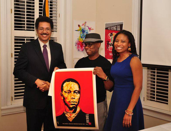 "Michael Thompson presents his Paul Boggle poster to the Jamaican Ambassador to the United States, Stephen Vasciannie. Next to him, Kathryn Buford, founder of ""Live Unchained""."