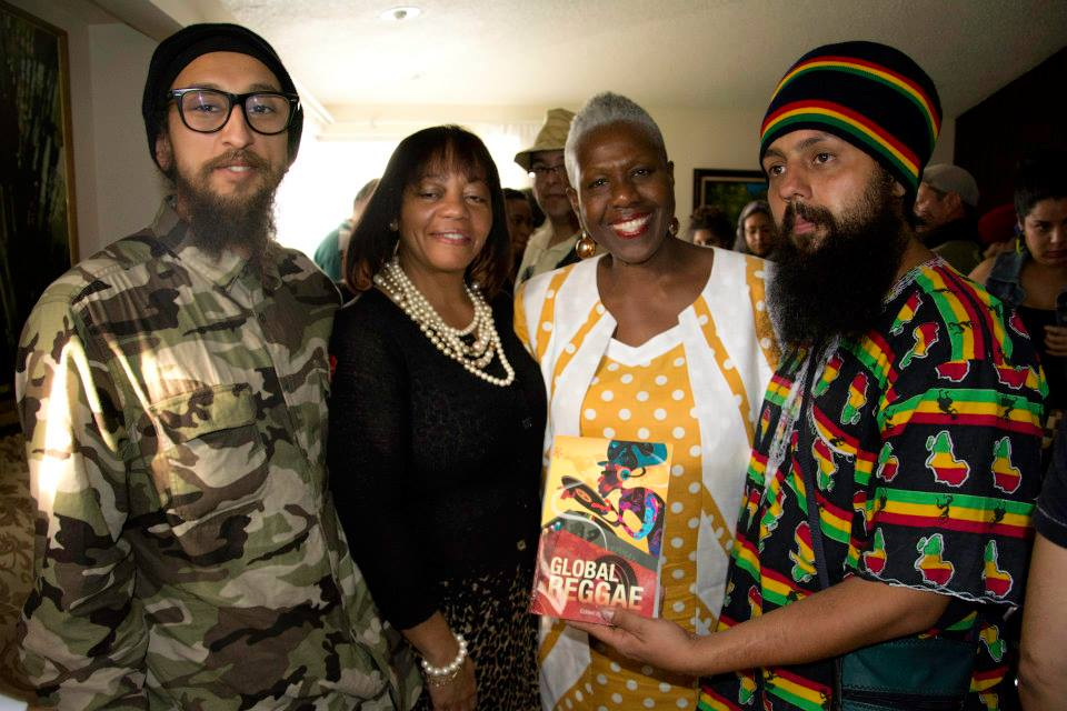 "Professor Carolyn Cooper pose with her book ""Global Reggae"" next to Sandra Grant Griffiths, JP, Ambassador of Jamaica and Rastafarians Ras Ariel (left) and Jah Levy (right)."